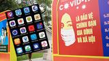 Hình minh hoạ: Tấm biển cổ động kêu gọi chống dịch COVID-19 trên đường phố Hà Nội và các ứng dụng phòng, chống dịch trên điện thoại ở VN