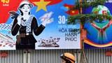 Hình minh hoạ. Áp phích cảnh báo dịch bệnh COVID-19 bên cạnh áp phích cổ động kỷ niệm 45 năm kết thúc chiến tranh trên đường phố Hà Nội, ngày 29/4/2020