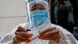 Một nhân viên y tế dán tên người được xét nghiệm vào ống xét nghiệm. Ảnh chụp tại Hà Nội, tháng 1 năm 2021.